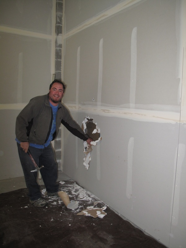 Go Alan Go! Our contractor breaks into the wall that will join the main store space with the food room
